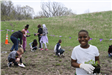 A 5th grade boy holding seedlings smile at the camera while other students plant milkweed in a field