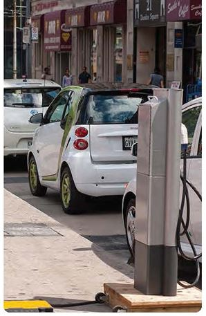 Smart cars parked along a street next to electric chargers
