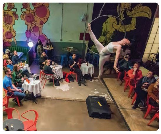 An aerial acrobat performs above people seated at tables