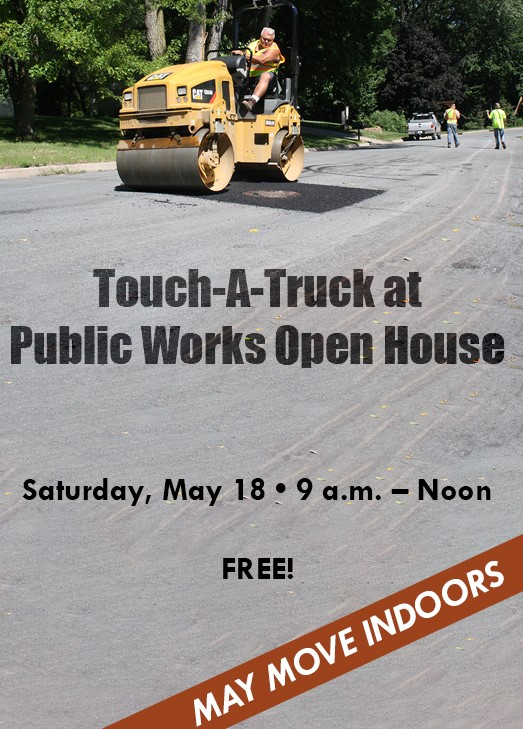 A man drives a roller over freshly laid asphalt. Text: Touch-A-Truck at Public Works Open House. Sat