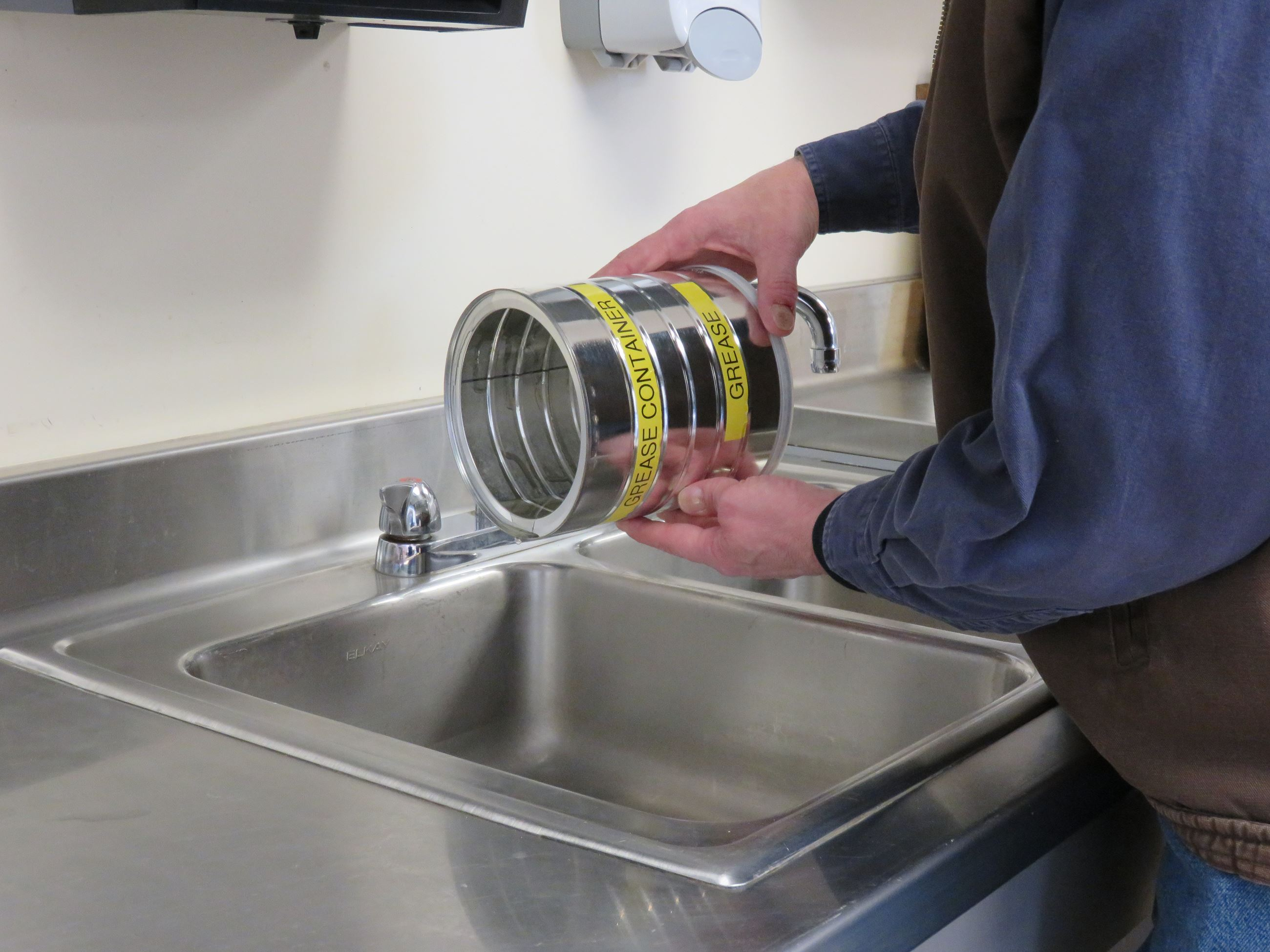 Person pouring grease from a coffee can-size grease collection container into the sink.