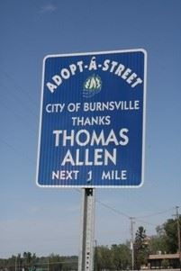 "Adopt-A-Street sign, blue with white lettering ""Thanks Thomas Allen, next 1 mile"""